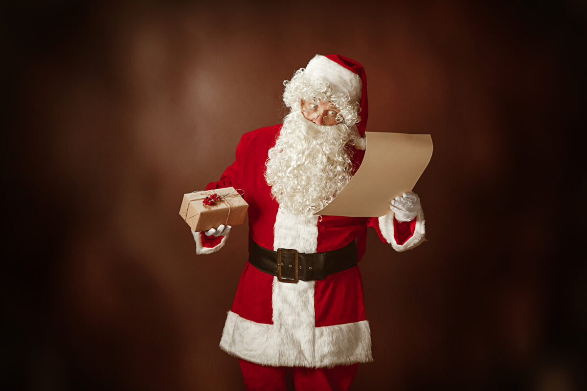 portrait-man-santa-claus-costume-with-luxurious-white-beard-santa-s-hat-red-costume-reading-letter-red-studio-background-with-gifts-1200x800.jpg